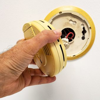 man hand opening up builtin smoke alarm