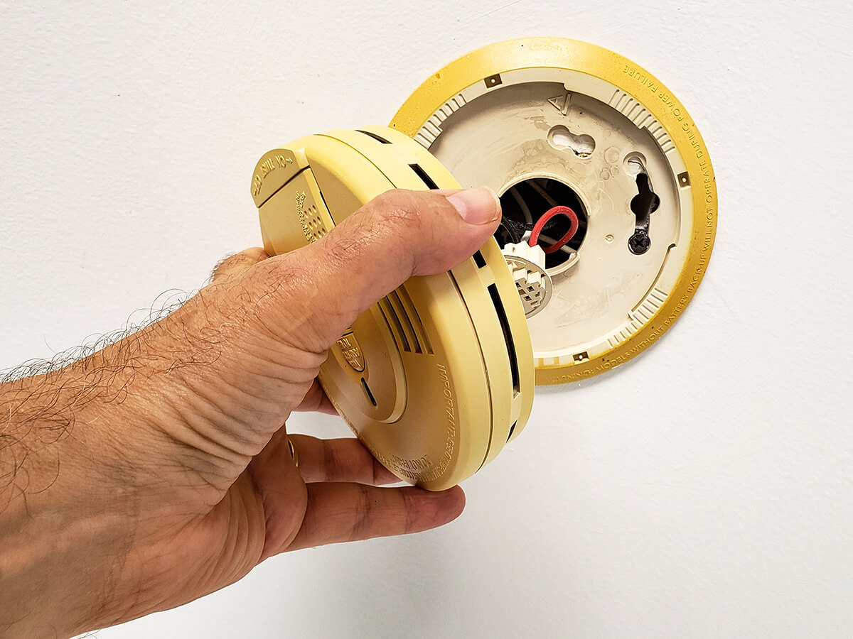 man hand opening up builtin smoke alarm