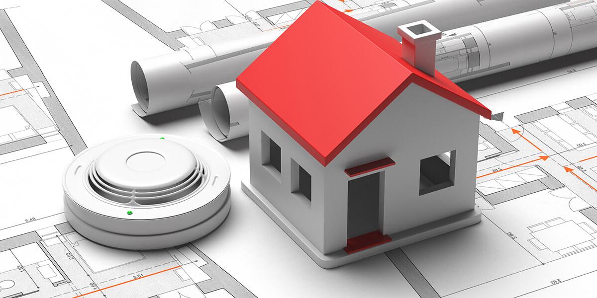 smoke detector and small house on blueprint
