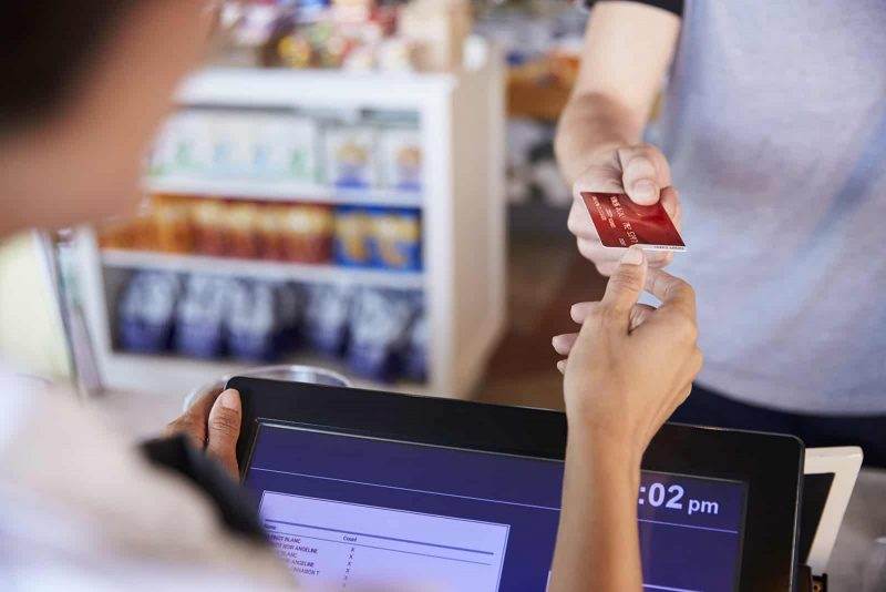 cashier-accepts-card-payment-from-customer-in-deli